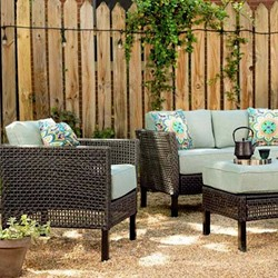 patio chair, sofa, and table in a back yard with a wooden fence