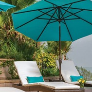 a blue patio umbrella by two patio chairs with matching pillows